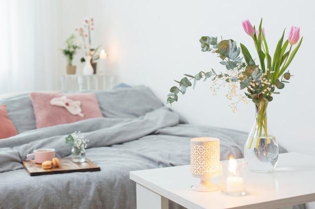 Interior de dormitorio con flores, velas y una taza de té.