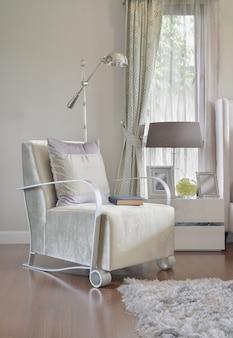 Interior de dormitorio moderno con almohada gris en el sillón y mesa de noche lámpara en casa