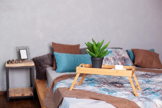 Interior del dormitorio con una pequeña mesa en la cama y una taza de café. bandeja de desayuno de madera en cama por la mañana. una taza de espresso en la mañana a la cama. luna de miel, sorpresa. aloe vera en una olla. decoración de la habitación