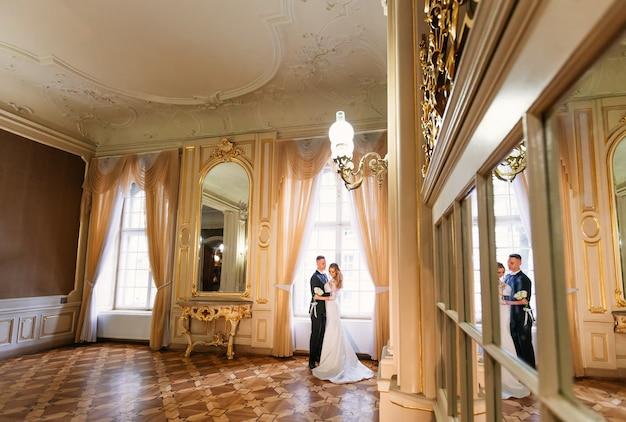 Interior elegante de la habitación con espejos y grandes ventanales. recién casados abrazándose junto a la ventana.