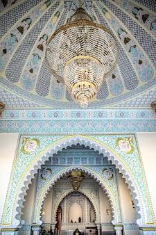 El interior es de estilo islámico tradicional con una gran lámpara de araña y muchos detalles y adornos.