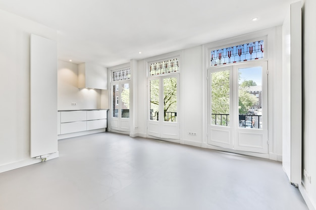 Interior de la espaciosa habitación luminosa con grandes ventanales ornamentales y mostradores en apartamento contemporáneo