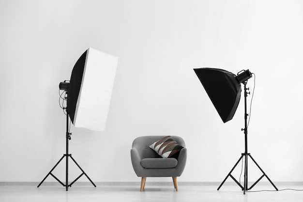 Interior del estudio fotográfico moderno con sillón y equipamiento profesional