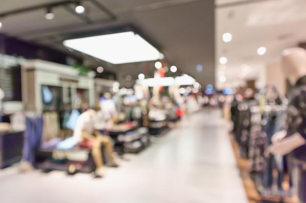 Interior de exhibición de boutique de ropa de desenfoque abstracto del fondo del centro comercial