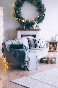 Interior de la habitación de año nuevo con chimenea, sofá y una gran corona de navidad sobre la chimenea.