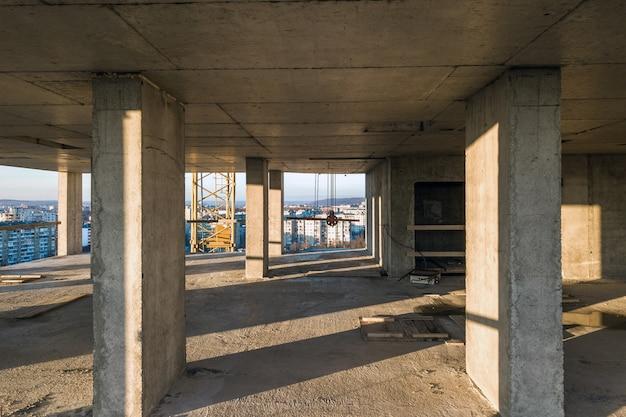 Interior de una habitación de edificio de apartamentos residenciales de hormigón con paredes desnudas sin terminar y pilares de soporte para futuras paredes en construcción.