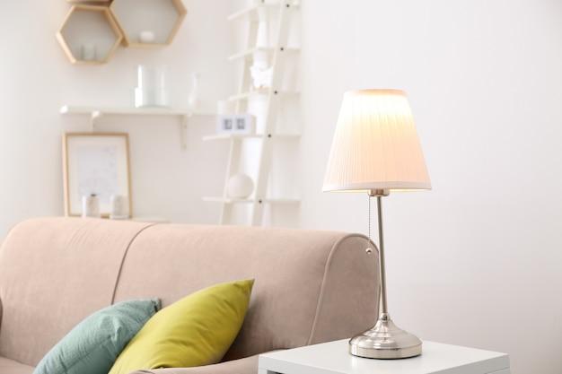 Interior de la habitación con elegante lámpara de mesa y cómodo sofá