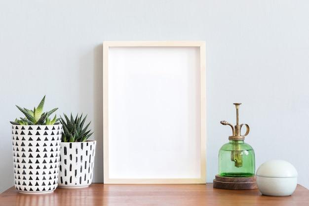 Interior de la habitación escandinava con marco de fotos en el estante de bambú marrón con hermosas plantas en diferentes macetas de diseño y hipster