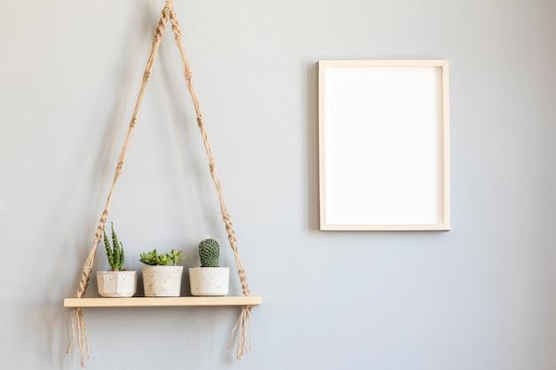 Interior de la habitación escandinava con marco de fotos con hermosas plantas en diferentes macetas de diseño y hipster