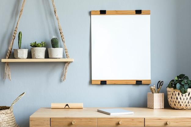 Interior de la habitación escandinava con marco de fotos en la mesa de bambú con hermosas plantas en diferentes macetas de diseño y hipster