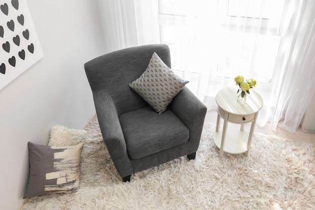 Interior de la habitación luminosa con sillón acogedor junto a la ventana