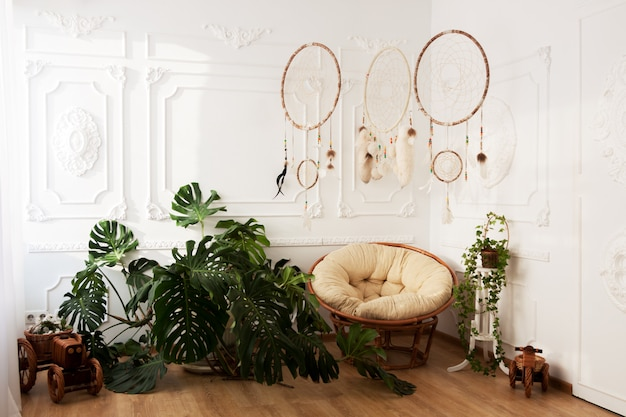 Interior de la habitación con plantas tropicales monstera, atrapasueños y silla de papasan.