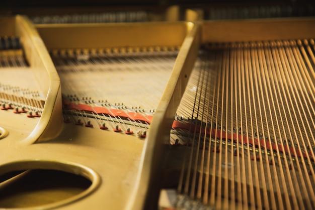El interior de un instrumento clásico de piano de cola con cuerdas de cable de cobre.