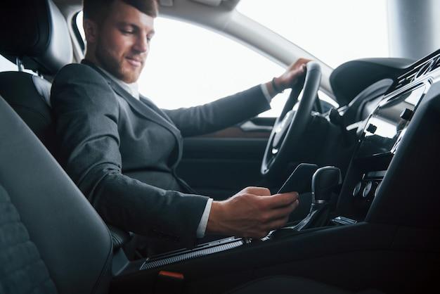 Interior de lujo. hombre de negocios moderno probando su nuevo coche en el salón del automóvil