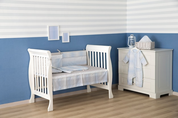 Interior de la luz acogedora sala de bebé con cuna y ropa de cama