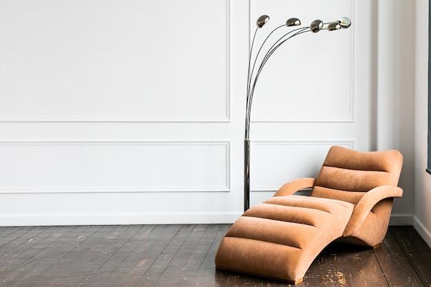 Interior minimalista de sala de estar en estilo clásico con copyspace. pared de yeso blanco decorada con molduras, moderno sofá y lámpara de pie sobre suelo de madera.