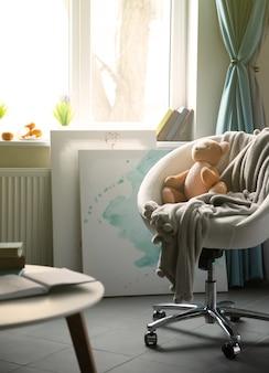 Interior de la moderna sala de estar en tonos grises con osito de peluche en la silla