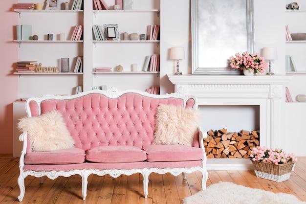 Interior moderno y luminoso con chimenea, flores de primavera y un acogedor sofá rosa.