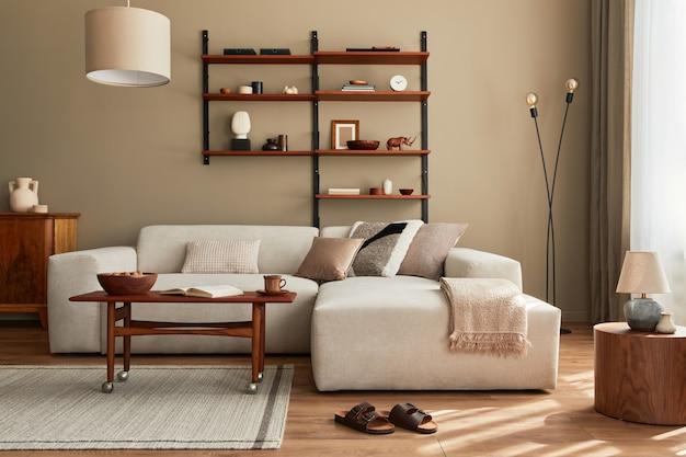 Interior moderno de salón con sofá beige modular de diseño, mesa de centro, muebles, lámpara colgante, estantería, zapatillas, alfombra, decoración y elegantes accesorios personales en la decoración del hogar.