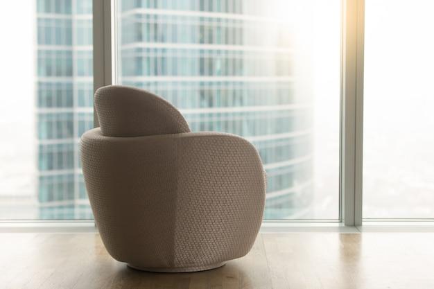 Interior moderno con silla de diseño cerca de la ventana de cuerpo entero