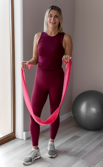 Interior mujer madura haciendo ejercicios cardiovasculares tiro largo