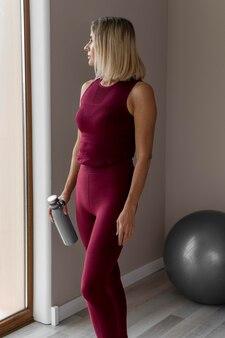Interior mujer madura de pie y sosteniendo una botella