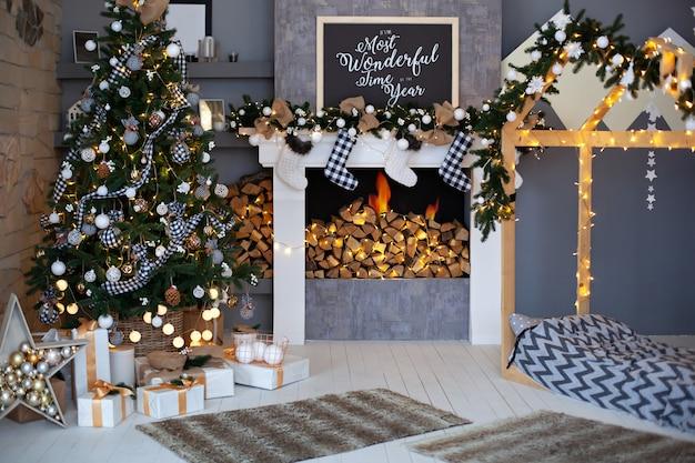 Interior de navidad de la sala de estar con árbol de navidad decorado, chimenea con calcetines de navidad y cama de madera en forma de casa. elegante interior de la habitación de los niños, decoración de la habitación en estilo loft rústico