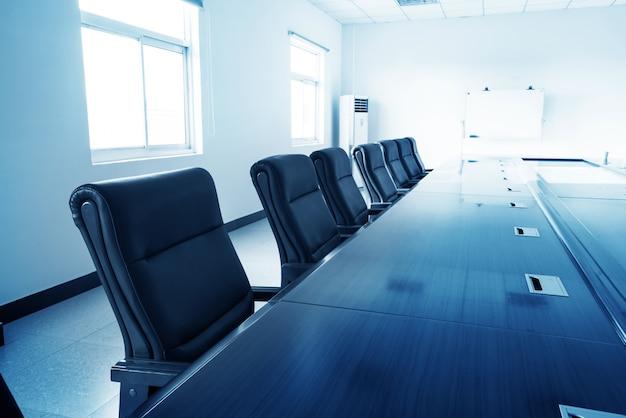 Interior de oficina con mesa y sillas.