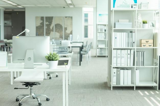 Interior de una oficina moderna con computadora y muebles blancos.