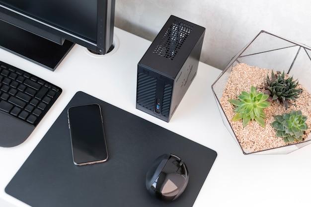 Interior de la oficina moderna. lugar de trabajo con teclado, mouse, teléfono y suculentas en mesa blanca.