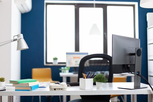 Interior de la oficina moderna sin nadie para que los empresarios trabajen. vista interior del elegante espacio del lugar de trabajo de inicio corporativo. supervise con gráficos y estadísticas financieras.