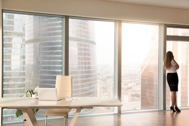 Interior de la oficina moderna con silueta femenina de pie en la ventana de cuerpo entero