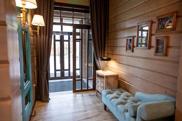 Interior de una pequeña y cómoda habitación con sofá de terciopelo suave y mesita de noche con lámpara a lo largo de la pared de madera por puerta abierta