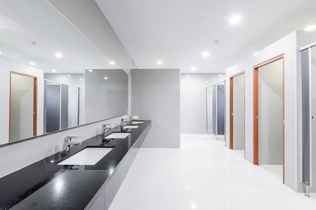 Interior público de baño con lavabo, lavabo, grifo, forrado.