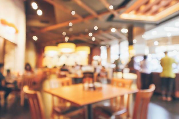 Interior del restaurante con mesa de madera y cliente desenfoque de fondo abstracto con luz bokeh