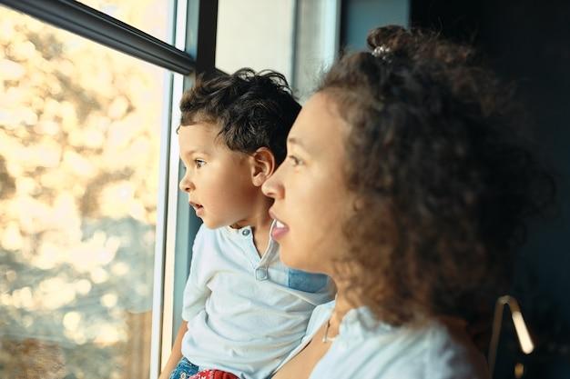 Interior retrato de feliz joven madre latina quedarse en casa de pie junto a la ventana con su hijo preescolar en sus brazos, mirando hacia afuera a través del vidrio