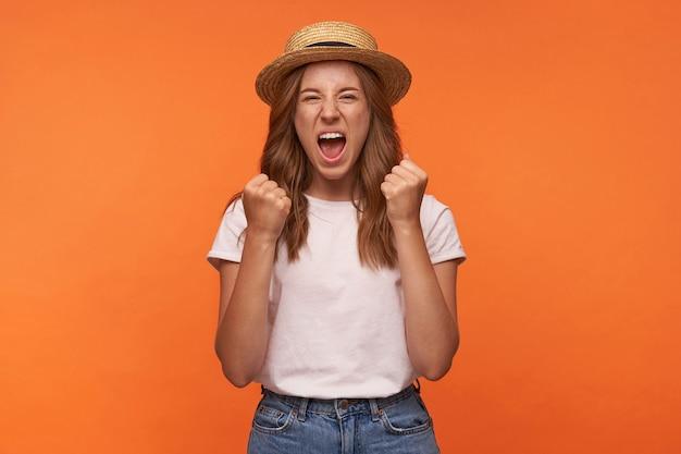 Interior retrato de joven alegre con cabello rojo levantando felizmente los puños apretados, mirando y gritando alegremente, posando