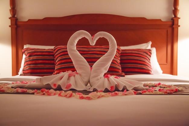 Interior romántico del dormitorio, toallas de origami de swan kissing y flor rosa rosa blanca fresca espolvoreada