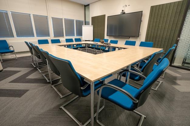 Interior de la sala de conferencias de una oficina moderna con paredes blancas y un monitor
