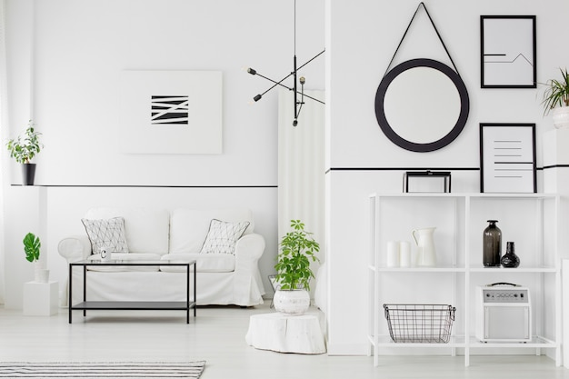 Interior de la sala de estar en blanco y negro con sofá, mesa, estantes, adornos, carteles y plantas