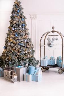 El interior de la sala de estar en el estilo de navidad con un gran abeto y regalos de navidad.