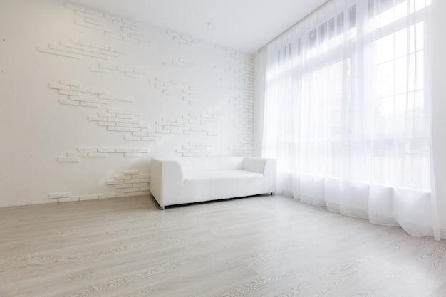 Interior de la sala de estilo moderno con sofá de tela, mesa auxiliar y pared blanca vacía