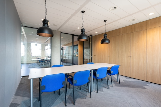 Interior de la sala de reuniones de una oficina moderna con una larga mesa de madera y sillas a su alrededor