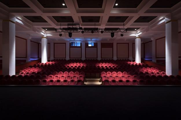 El interior de la sala en la vista del teatro o cine desde el escenario con luz apagada