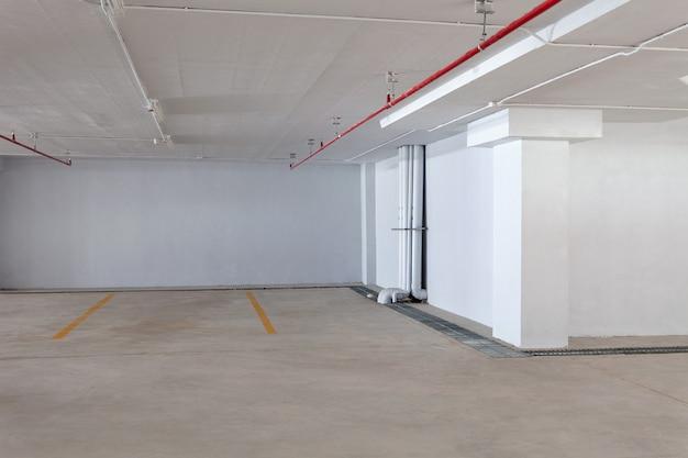 Interior subterráneo del garaje de estacionamiento nuevo vacío en la oficina del edificio del apartamento o del negocio y tienda del supermercado