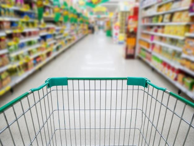 Interior del supermercado, pasillo del supermercado con carrito de compras verde vacío