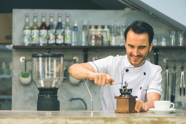 Interior tiro de joven macho barista haciendo una taza de café mientras está de pie detrás del mostrador de café. joven verter la leche en una taza de café.