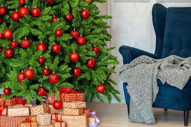 Interior de vacaciones hermoso árbol de navidad decorado con sillón azul