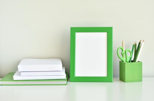 Interior verde de la sala de niños, maqueta de marco de fotos, libros, útiles escolares en la mesa blanca.
