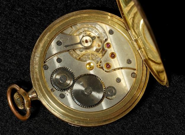 Interior de un viejo reloj de bolsillo con movimiento mecánico de cuerda manual.